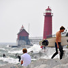 SURFER ON THE ROCKS AT GRAND HAVEN LIGHTHOUSE