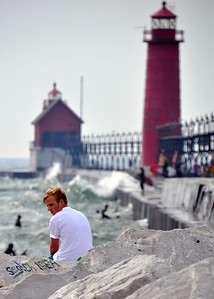 A GUY CHILLING ON THE ROCKS AT THE GRAND HAVEN LIGHTHOUSE