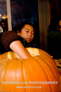 "Madi cleaning out the pumpkin gut and ""harvesting"" the seeds."