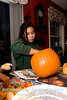 """Rachel cleaning out the pumpkin gut and """"harvesting"""" the seeds."""