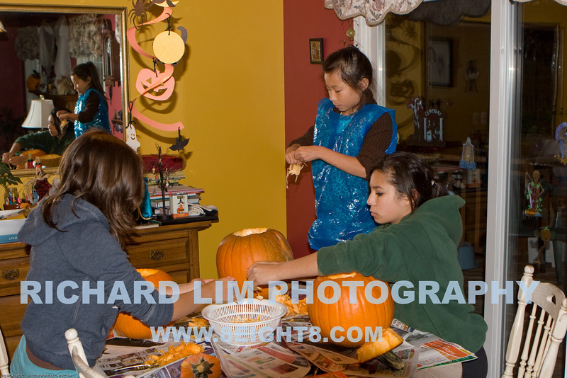The Lim girls carving pumpkins from the Howell Farmers Market. Katie (back to camera), Madi (in blue plastic smock) and Rachel.