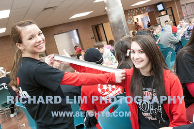 Kacie Sanderson measuring a length of duct tape after Senior, Lauren Boyce, donated to the cause.