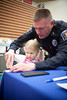 Officer Gary Mitts assisting Adelyn Palmer, age three and a half in the fingerprinting process as part of the Howell Police Dept free Kids ID program.