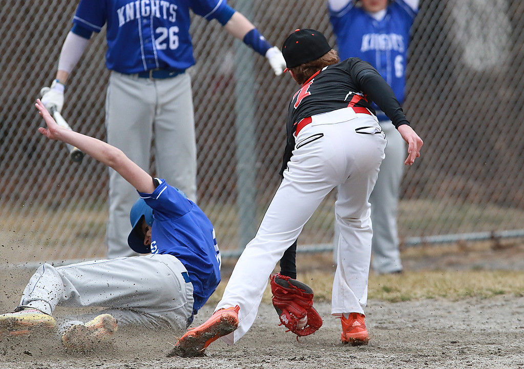 . Lunenburg Middle High School baseball played Gardner High School on Friday afternoon, April 12, 2019. LMHS\'s Colin Garrity slides into home safe as GHS\'s pitcher Kyle Samson just missed him with the tag. SENTINEL & ENTERPRISE/JOHN LOVE
