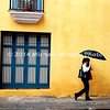 Cuban Woman with umbrella against yellow wall