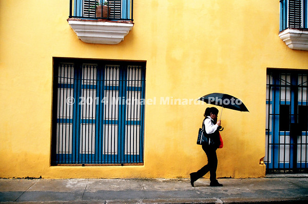 Cuban Woman with umbrella against yellow wall retouched 08930018