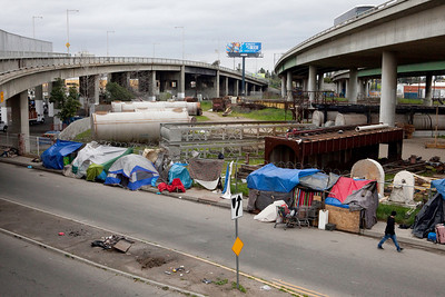 FRESNO, CA--- A man walks by a homeless camp on G Street under a Highway 41 overpass in South Fresno. Most of the homeless in Fresno make their abode in and around the area.