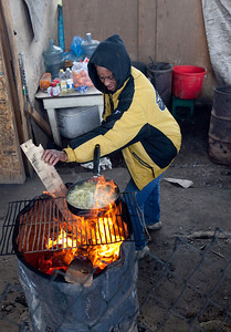 FRESNO, CA--- Pat Jackson from East Harlem New York stokes a fire as she makes some fresh french fries.  Jackson said she is homeless by choice and has been so for two years. She lives in an encampment  under the Highway 41 overpass in South Fresno.