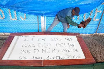 FRESNO, CA--- Ray Polk cleans off a sign he made with a scripture from the bible written on it in front of his homeless compound.  Polk is a one-man homeless shelter and provides food, clothing, counseling, shelter, and recently has erected a memorial under the Highway 41 overpass in an encampment in South Fresno to honor the homeless  who have passed away. Polk has made 77 markers  and has plans to make for 23 more.  Polk can tell  a story about how each of those memorialized and how the met their demise.