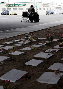 FRESNO, CA--- A homeless man walks by a memorial erected by Ray Polk under the Highway 41 overpass in an encampment in South Fresno to honor the deceased homeless. There are 77 markers  and Polk has plans for  23 more.