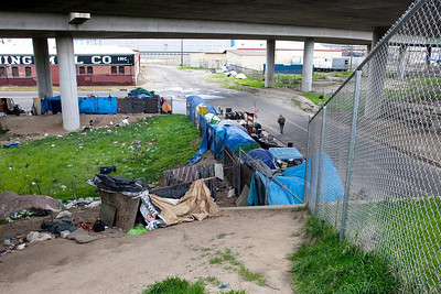 FRESNO, CA--- A man walks by part of a homeless encampment under the Highway 41 overpass in South Fresno. Most of the homeless in Fresno live in and around this area.