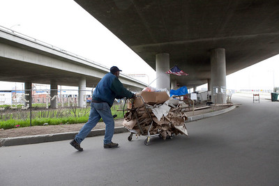 FRESNO, CA--- Ray Polk pushes a cart of cardboard he is going to sell in front of his homeless compound.  Polk is a one-man homeless shelter and provides food, clothing, counseling, shelter, and recently has erected a memorial under the Highway 41 overpass in an encampment in South Fresno to honor the homeless  who have passed away. Polk has made 77 markers  and has plans to make for 23 more.  Polk can tell  a story about how each of those memorialized and how the met their demise.