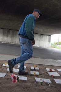 FRESNO, CA---Ray Polk walks by a memorial  he constructed under the Highway 41 overpass in an encampment in South Fresno to honor the deceased homeless. Polk made the memorials out of scrap wood which he painted and wrote their names on them with a marker. There are 77 markers  and Polk has plans for  23 more.