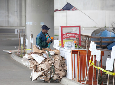 FRESNO, CA--- Ray Polk cleans off an orange in front of his homeless compound.  Polk is a one-man homeless shelter and provides food, clothing, counseling, shelter, and recently has erected a memorial under the Highway 41 overpass in an encampment in South Fresno to honor the homeless  who have passed away. Polk has made 77 markers  and has plans to make for 23 more.  Polk can tell  a story about how each of those memorialized and how the met their demise.