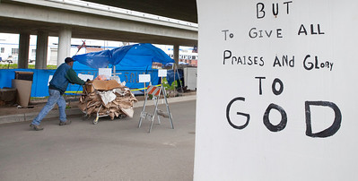 FRESNO, CA--- Ray Polk pushes a cart of cardboard he is going to sell in front of his homeless compound.  Polk is a one-man homeless shelter and provides food, clothing, counseling, shelter, and recently has erected a memorial under the Highway 41 overpass in an encampment in South Fresno to honor the homeless  who have passed away. Polk has made 77 markers  and has plans to make for 23 more.