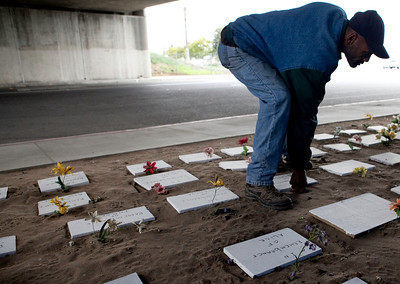 FRESNO, CA--- Ray Polk plants a a plastic flower at the homeless  memorial he erected under the Highway 41 overpass in an encampment in South Fresno to honor the homeless  who have passed away. Polk has made 77 markers with plans for  23 more. Polk can tell you a story about each of the deceased homeless people who are often known by a nickname or by their first name.