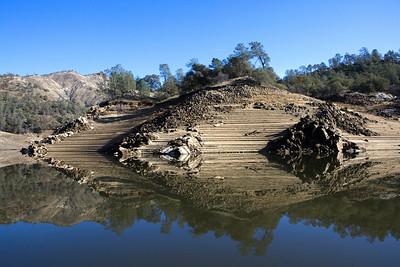 Friant,CA--- The shore of Millerton Lake reflects like glass on Monday, Dec. 14, 2009  revealing a terraced shore shaped by declining water levels. Millerton Lake was created by Friant Dam on the San Joaquin River, about 15 miles north of Fresno. It is an irrigation reservoir, built by the Bureau of Reclamation in 1942. The Friant Water Authority has proposed  a new reservoir and dam at Temperance Flat. Millerton Lake is just West of the proposed reservoir. The price tag for the project is some $3.36 billion and could be built in 15 years.  It would provide 1,200,000 acre-feet of storage and an additional 160,000 acre-feet of usable annual water. Critics of the dam and reservoir say that the price tag is too high and it can't be proven that their will be a sufficiently large enough urban demand for the high-priced water that will be sold. Photo by Tomas Ovalle