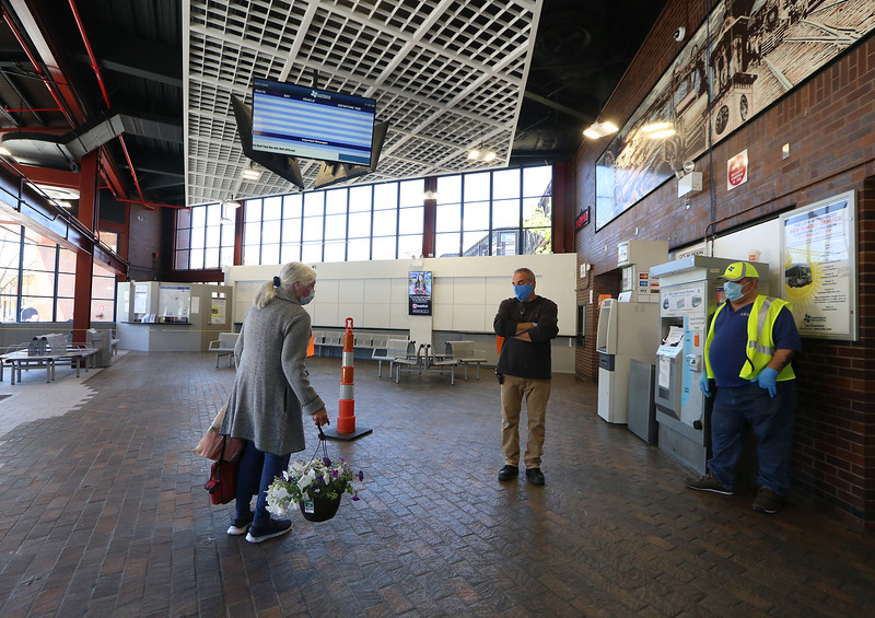 From left, Naomi Weitzman of Lowell, with some petunias she'd bought at Walmart, talks with facilities manager Todd Bello, center, and Mark Patten of Lowell, who works security, in an otherwise empty Lowell Regional Transit Authority terminal in Lowell. LRTA has received a grant to help with COVID-19 related expenses and lost revenue. (SUN/Julia Malakie)