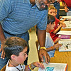"Thomas Peeks, president of Lamorinda Sunrise Rotary, helps pupil at Springhill Elementary School in Lafayette look up word ""service"" in dictionaries the club gave to every third-grader at each of the four public elementary schools in Lafayette. At a later date, their counterparts attending private schools will receive their personal copies. [CREDIT Thomas Black]"