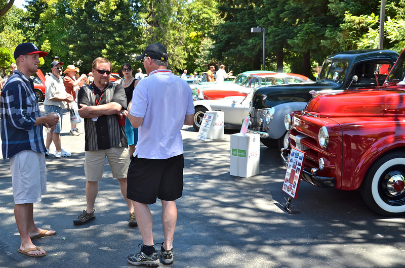 """Larry Blodgett (sunglasses), who displayed this 1952 red Dodge panel van, chats with two of the hundreds to attend the daylong exhibition. The half-ton """"Job-Rated"""" van is company vehicle for Blodgett's Abbey Carpet in Lafayette. According to its owner, the van is """"99 percent restored."""" It sold new for $1,754.15."""