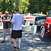 "Larry Blodgett (sunglasses), who displayed this 1952 red Dodge panel van, chats with two of the hundreds to attend the daylong exhibition. The half-ton ""Job-Rated"" van is company vehicle for Blodgett's Abbey Carpet in Lafayette. According to its owner, the van is ""99 percent restored."" It sold new for $1,754.15."