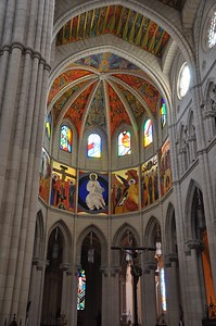 The colorful ceiling and stained glass windows inside the Cathedral de Almudena above the crucifix.