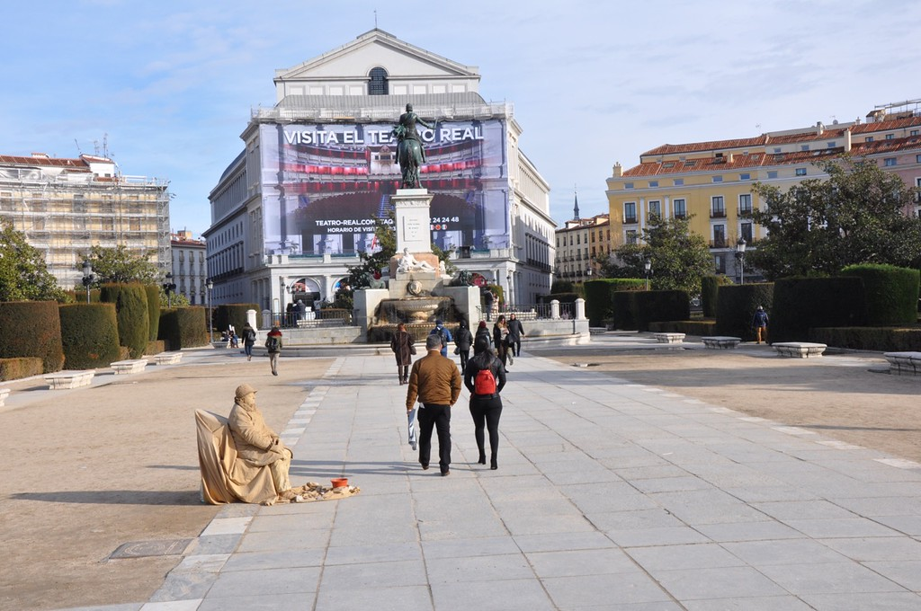 This plaza leads away from the Royal Palace in Madrid. Note the real statue and the street performer posing as a statue. She moves when you drop a Euro in her cup