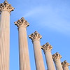 The columns of the Roman Temple in Córdoba against a blue sky. The columns, like much of the temple, are made of marble.