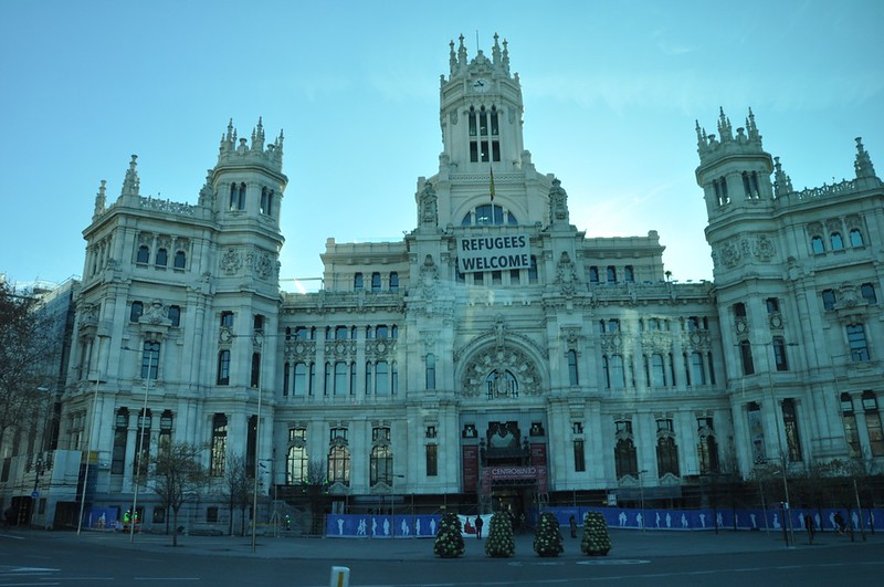 """The Madrid City Hall. This is the newer city hall, replacing the one found closer to Plaza Mayor. The sign which reads """"Refugees Welcome"""" is in response to the Syrian civil war and the large number of people fleeing the country for their own safety."""