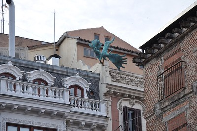 Statues adorn the tops of many buildings in Madrid. This one is of a fallen angel.