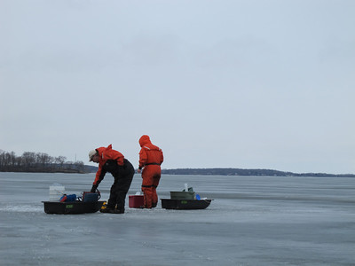 Ted Bier, senior research specialist and Dave Harring, facilities manager, prepare to drill through the ice and take samples for the LTER project.