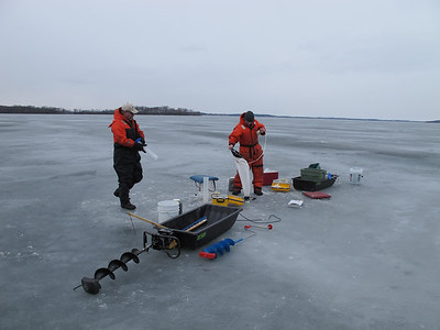After breaking through the ice, Bier prepares to drop a zooplankton net into the lake.