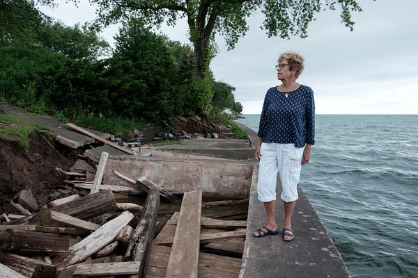 In this June 23rd, 2017 photo Judy Brounscheidel looks over the remains of her patio along Lake Ontario. Rising Lake levels  claimed close to 20 feet of her property in Somerset, N.Y. Tuesday, the President Trump declared a major disaster for areas in  Niagara, Oswego, Jefferson, St. Lawrence, Orleans, and Wayne Counties (Joed Viera/Lockport Union-Sun & Journal)