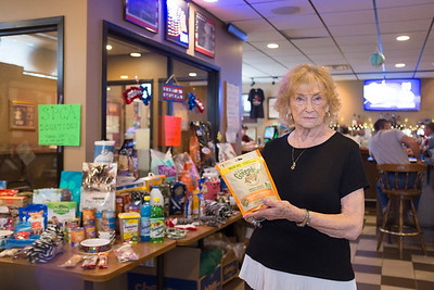 JOED VIERA/STAFF PHOTOGRAPHER- Gayle Chalfin holds up a packet of dental treats she donated to Heather Haley's SPCA fundraiser at the Navy Marine Club.