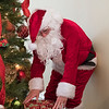 Joed Viera/Staff Photographer- Santa Clauss places presents under the Kenan House Christmas Tree.  Mr Clauss and his wife will be at the Kenan Center's annual Holiday Gift Show that takes place this weekend.