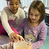 "JOED VIERA/STAFF PHOTOGRAPHER-  Isabella Gibbs, 7, and Lily Caldwell, 8, made baking soda-covered gummi worms ""dance"" in a glass of vinegar in an experiment during a STEM lab at the YMCA's Easter Break Day Camp on Wednesday."