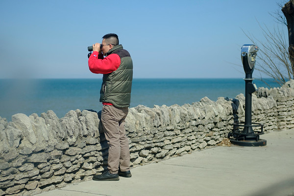 JOED VIERA/STAFF PHOTOGRAPHER-Jin Lin, a chinese tourist stops by Olcott Beach to test his new binoculars on Monday afternoon. After scanning Lake Ontario for a bit he stopped to admire the Toronto skyline in the distance