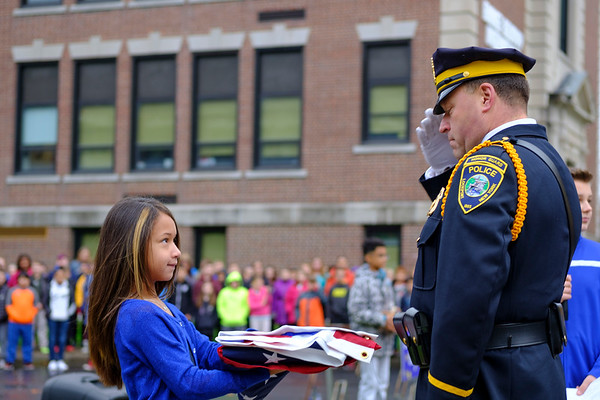 Joed Viera/Staff Photographer-Alanis Cintron-Zambrana hands a folded flag to Sal Licata during the flag raising ceremony to honor fallen Buffalo Police Officer Craig Lehner at Emmet Belknap  Monday morning.