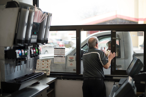 Joed Viera/Staff Photographer-James Graziano works the drive thru at Arby's on Transit Road. Graziano has been a manager at the store for 33 years.