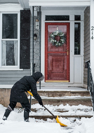 Joed Viera/Staff Photographer-Heidi Jeffery shovels snow off of the steps of her Erie Street home.