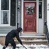 Joed Viera/Staff Photographer-Heidi Jeffery shovels snow off of the steps of her Erie Street home.