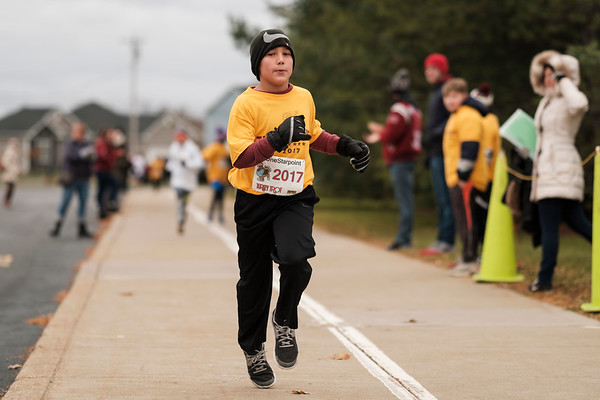 "Joed Viera/Staff Photographer- <br /> Noah Simpson, 10, finishes the Turkey Trot in first place for the second year in a row. His secret? ""It's in my family's blood. My mom was a hurdle runner."" Simpson said."