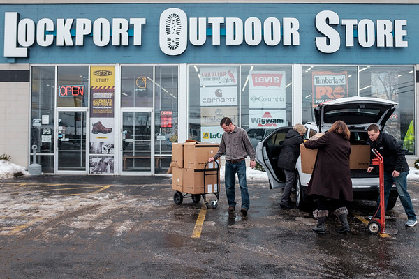 JOED VIERA/STAFF PHOTOGRAPHER-Lockport, NY-Charlie Haungs and Matt Stawicki help Kathy Jackson and Mary Brennan-Taylor load up SUV's with boxes filled with winter boots donated by the Lockport Outdoor Store to the YWCA.