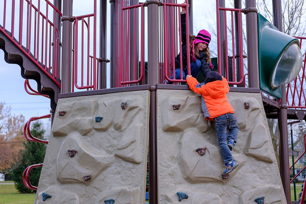 Joed Viera/Staff Photographer-  Maycle Bowes, 7, helps Erik Caldwell, 4, up the climbing wall at Day Road Park.