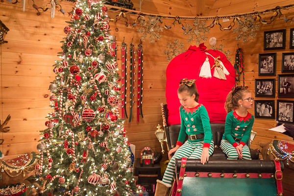 Joed Viera/Staff Photographer-Isabella and Julianna Pearl take a ride on Santa Claus' sleigh in his Christmas Cottage at Day Road Park Thursday evening.