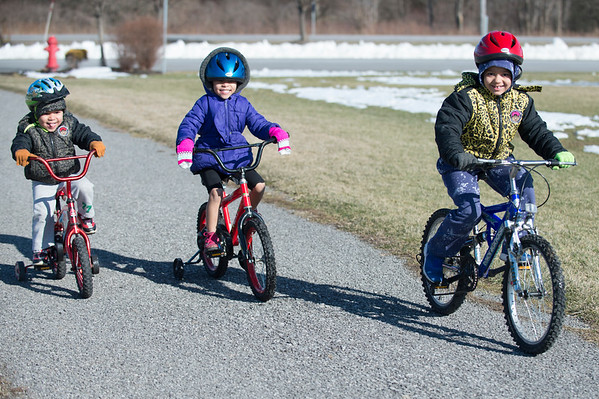 Joed Viera/Staff Photographer-Ezra Markovich, 3, Nancy Tidwell, 5, and<br /> Elijah Patrick, 6, ride their bikes down the trail at Day Road Park.