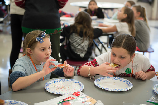Joed Viera/Staff Photographer- Addisin Healy, 8, and Camryn Taylor, 8, enjoy Christmas cookies during Starpoint's Winterfest. Winterfest is a yearly tradition where the school's juniors and seniors organize fun holiday activities for kids in kindergarten through fifth grade, this years theme was Grinchmas.