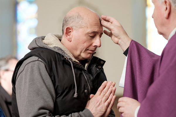 JOED VIERA/STAFF PHOTOGRAPHER-Lockport, NY-Lawrence Spadaccia recieves ashes from Father Walter J. Szczesny at All Saints Roman Catholic Parish. Traditionally a cross of ashes is placed on parishioners foreheads marking the start of Lent.