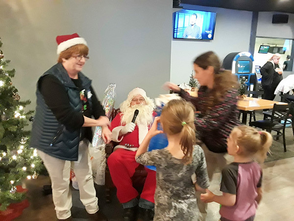 CONTRIBUTED-Lockport Kiwanian Secretary and Treasurer Diane Hoffman-Pivetz helps Santa pass out gifts to a family of participants during the Kiwanian Christmas Party at Brad Angelo Lanes.