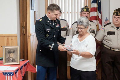 JOED VIERA/STAFF PHOTOGRAPHER-Connie Caldwell accepts the bronze star on behalf of her brother who went missing in action during WWII.